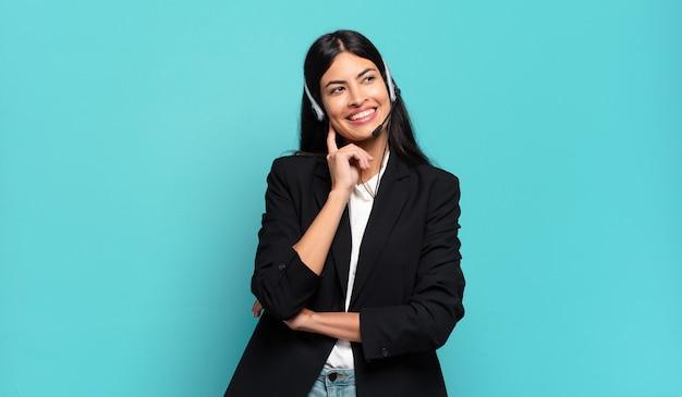 Junge hispanische telefonverkäuferin, die glücklich lächelt und träumt oder zweifelt und zur seite schaut