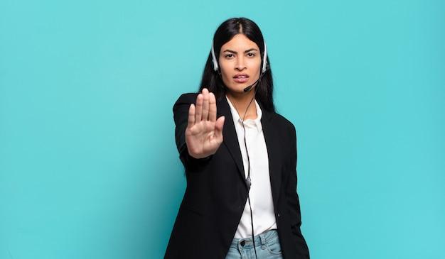 Junge hispanische telemarketerin, die ernst, streng, unzufrieden und wütend aussieht und offene handfläche zeigt, die stoppgeste macht
