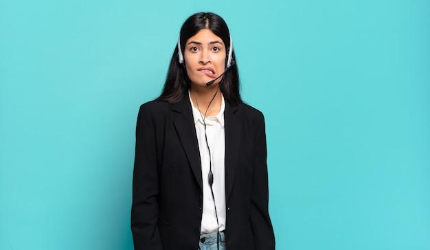 Junge hispanische telemarketerin, die verwirrt und verwirrt aussieht, sich mit einer nervösen geste auf die lippe beißt und die antwort auf das problem nicht kennt