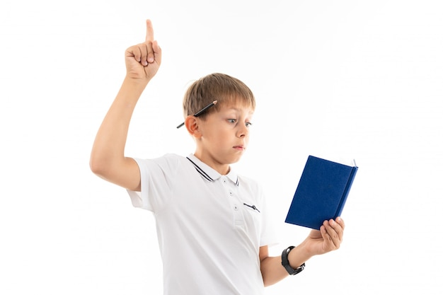 Junge hob den finger, während er ein buch über weiß las