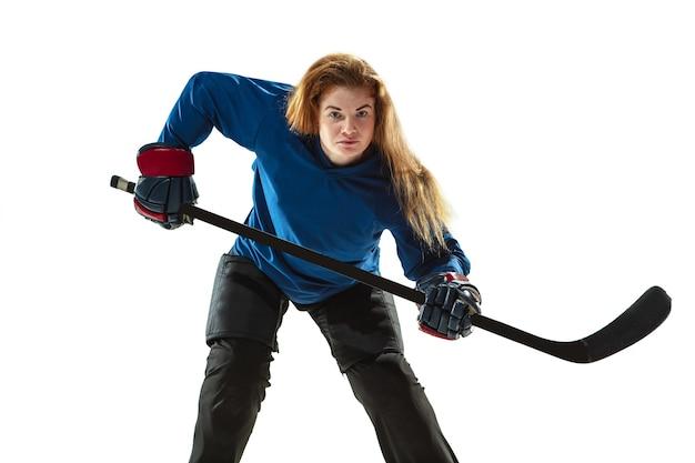 Junge hockeyspielerin mit dem stock auf dem eisplatz und der weißen wand