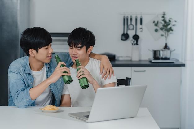 Junge homosexuelle paare trinken bier bei der anwendung des computerlaptops am modernen haus. die glücklichen asiatischen lgbtq-männer entspannen sich spaß unter verwendung des technologiespielsocial media beim sitzen der tabelle in der küche am haus.