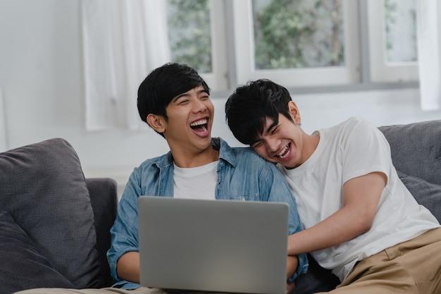 Junge homosexuelle paare unter verwendung des computerlaptops am modernen haus. das glückliche asiatische lgbtq + -männer entspannen sich spaß unter verwendung des aufpassenden films der technologie im internet zusammen, während lügensofa im wohnzimmer am haus.