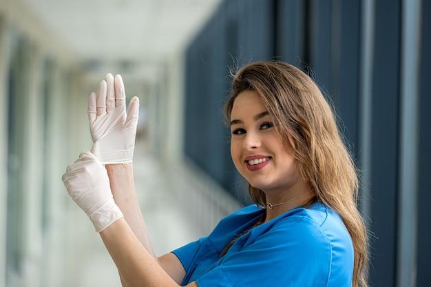 Junge hübsche ärztin in blauer uniform mit schützenden weißen handschuhen, um die ausbreitung des coronavirus zu verhindern