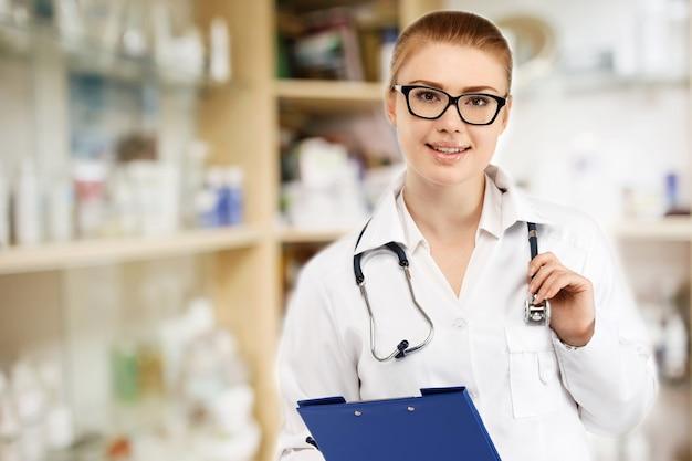 Junge hübsche ärztin in weißer uniform auf verschwommenem medizinschrank und speichert medizin- und apotheken-drogerie für hintergrund