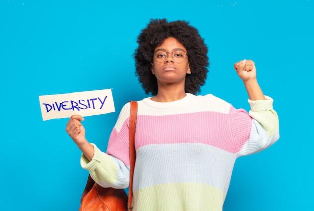 Junge hübsche afro-frau, die diversity-konzeptfahne hält