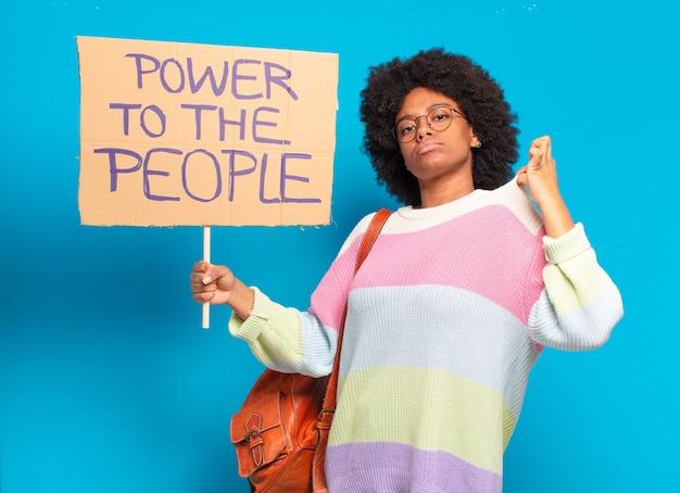 Junge hübsche afro-frau, die mit einer macht zum volksbanner protestiert