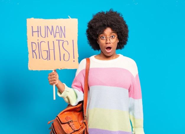 Junge hübsche afro-frau, die mit menschenrechtsfahne protestiert