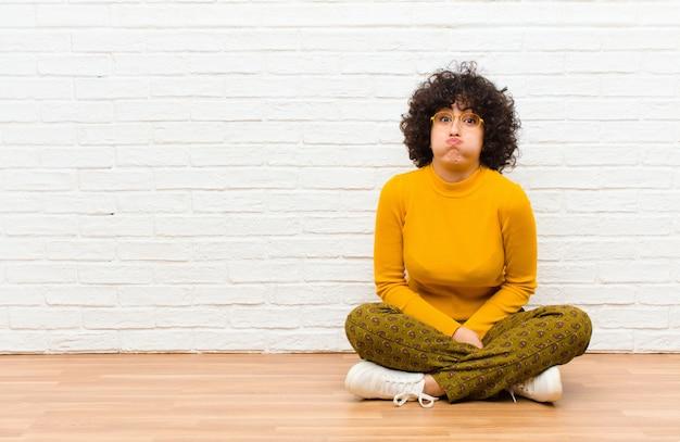 Junge hübsche afro-frau mit einem albernen, verrückten, überraschten ausdruck, pochenden wangen, sich gestopft, fett und voller essen auf dem boden sitzend
