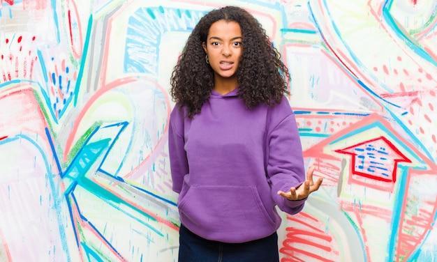 Junge hübsche afroamerikanerfrau, die wütend gegen graffitiwand schaut