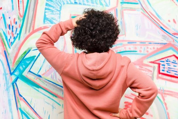 Junge hübsche afrofrau, die ahnungslos und verwirrt sich fühlt und eine lösung, mit der hand auf hüfte und anderer auf kopf, hintere ansicht gegen graffitiwand denkt