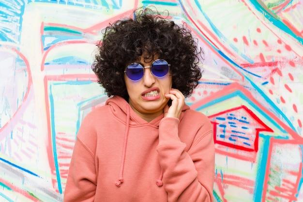Junge hübsche afrofrau, die betont, frustriert und müde sich fühlt und schmerzhaften hals, mit einem besorgten, gestörten blick gegen graffitiwand reibt