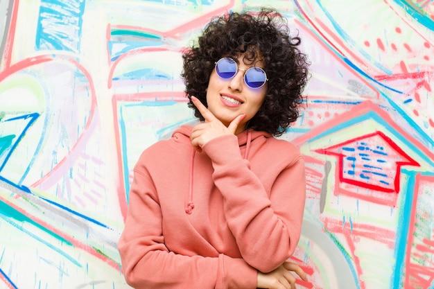 Junge hübsche afrofrau, die nachdenklich sich fühlt, ideen sich wundert oder sich vorstellt, oben zur copyspace graffitiwand träumt und schaut