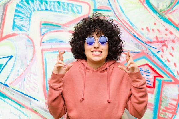 Junge hübsche afrofrau, die nervös und hoffnungsvoll sich fühlt, finger kreuzt, für gutes glück gegen graffitiwand betet und hofft