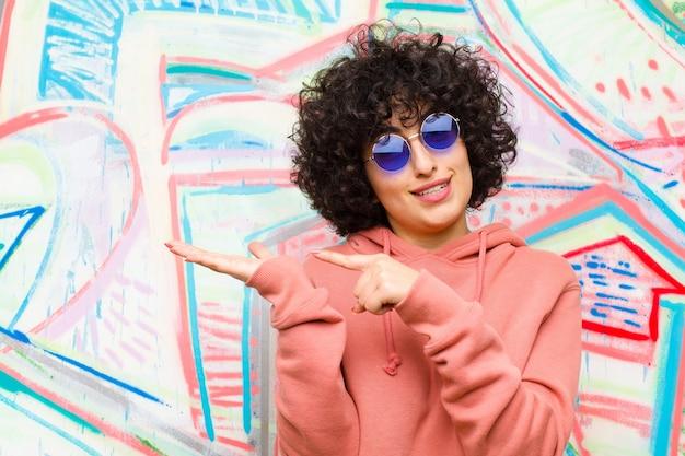 Junge hübsche afrofrau, die nett lächelt und auf kopienraum auf palme auf der seite zeigt, einen gegenstand gegen graffitiwand zeigt oder annonciert