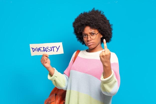Junge hübsche afrofrau, die papier mit diversity-konzeptfahne hält