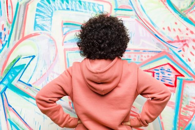 Junge hübsche afrofrau, die verwirrt oder voll oder die zweifel und fragen sich fühlen und wundern, mit den händen auf hüften, hintere ansicht gegen graffitiwand