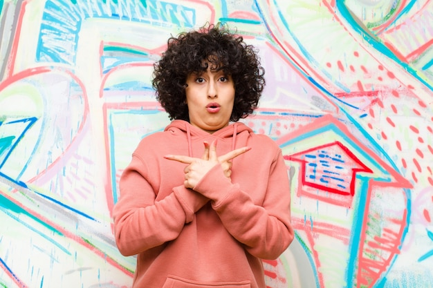 Junge hübsche afrofrau, die verwirrt und verwirrt schaut, in entgegengesetzte richtungen mit zweifeln gegen graffiti unsicher und zeigt