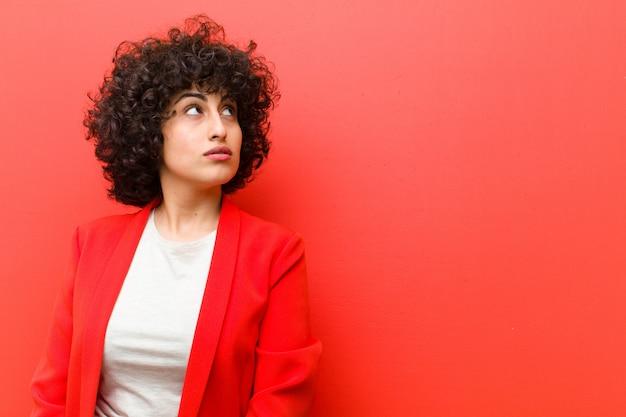 Junge hübsche afrofrau mit einem besorgten, verwirrten, ahnungslosen ausdruck, oben schauend, um den raum zu kopieren und zweifeln