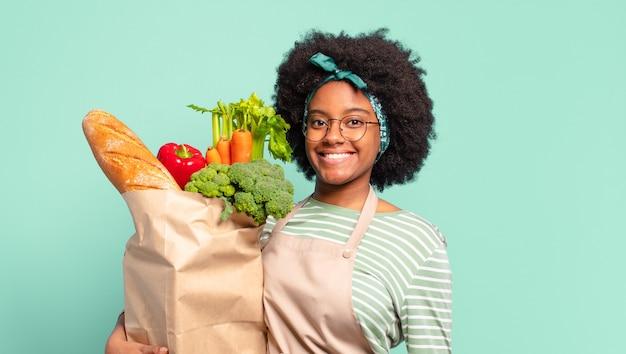 Junge hübsche afrofrau mit einer gemüsepapiertüte