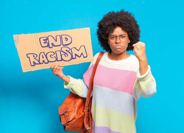 Junge hübsche afrofrau mit ende rassismus board