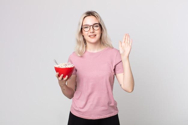 Junge hübsche albino-frau, die glücklich lächelt, die hand winkt, sie mit einer frühstücksschüssel begrüßt und begrüßt?