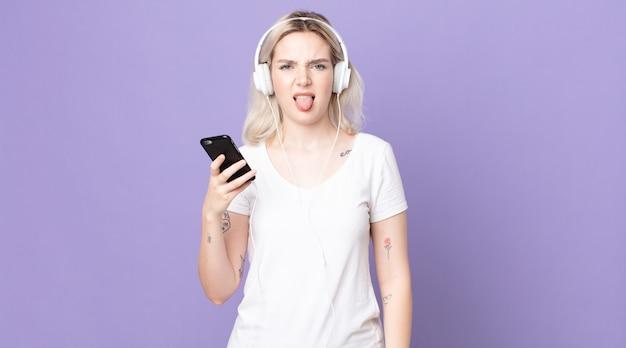 Junge hübsche albino-frau, die sich angewidert und irritiert fühlt und mit kopfhörern und smartphone die zunge herausstreckt