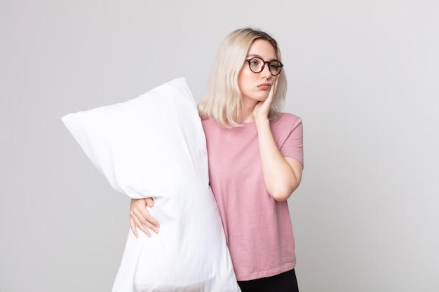 Junge hübsche albino-frau, die sich gelangweilt, frustriert und schläfrig fühlt, nachdem sie einen ermüdenden schlafanzug trägt und ein kissen hält