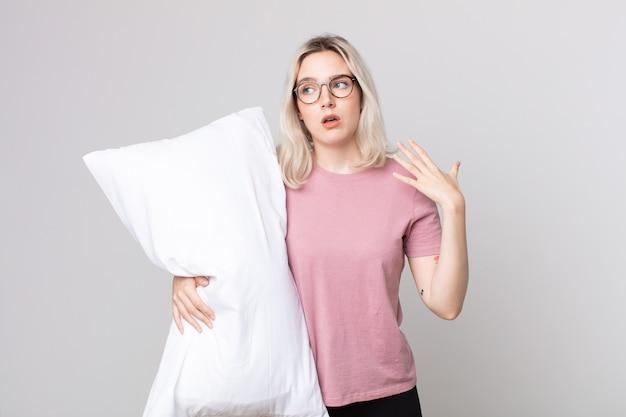 Junge hübsche albino-frau, die sich gestresst, ängstlich, müde und frustriert fühlt, trägt pyjamas und hält ein kissen