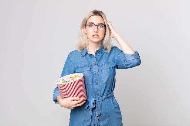 Junge hübsche albino-frau, die sich gestresst, ängstlich oder verängstigt fühlt, mit den händen auf dem kopf mit einem popcorn-eimer