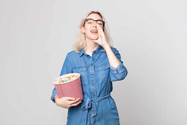 Junge hübsche albino-frau, die sich glücklich fühlt und mit den händen neben dem mund mit einem popcorn-eimer einen großen schrei ausstößt