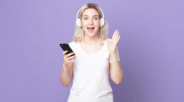 Junge hübsche albino-frau, die sich glücklich und erstaunt über etwas unglaubliches mit kopfhörern und smartphone fühlt