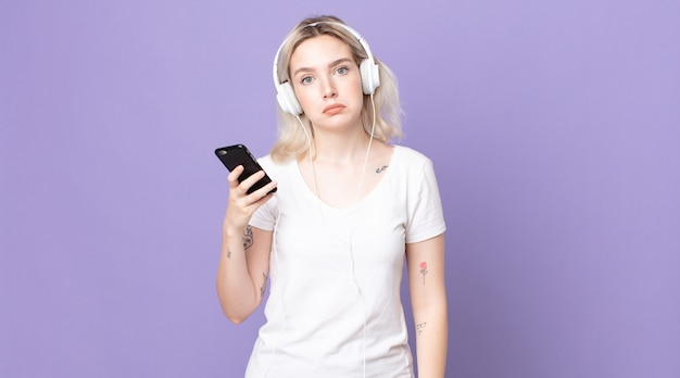 Junge hübsche albino-frau, die sich traurig und weinerlich mit einem unglücklichen blick fühlt und mit kopfhörern und smartphone weint