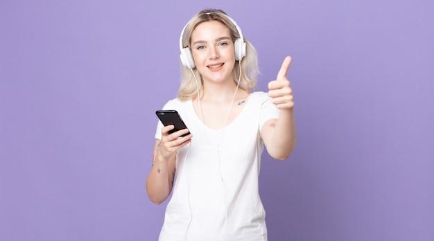 Junge hübsche albino-frau, die stolz ist und positiv mit daumen nach oben mit kopfhörern und smartphone lächelt