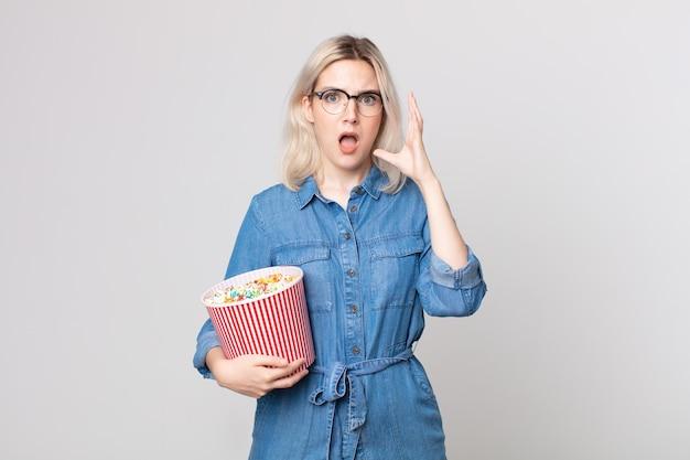 Junge hübsche albino-frau schreit mit den händen in die luft mit einem popcorn-eimer