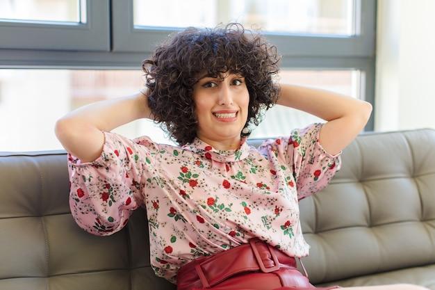 Junge hübsche arabische frau, die auf einem ledersofa sitzt