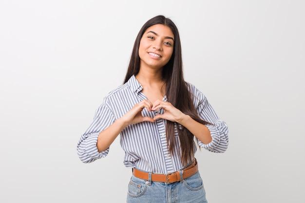 Junge hübsche arabische frau, die eine herzform mit den händen lächelt und zeigt.