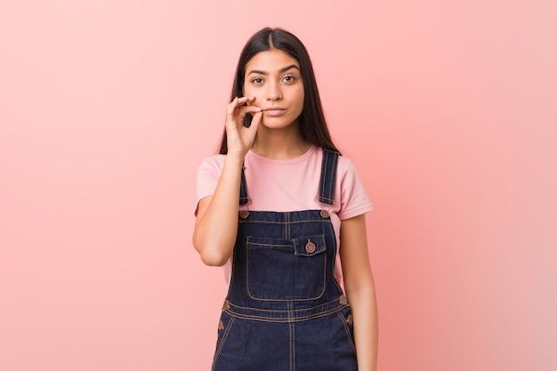 Junge hübsche arabische frau, die eine jeans-latzhose mit fingern auf den lippen trägt, die ein geheimnis halten.