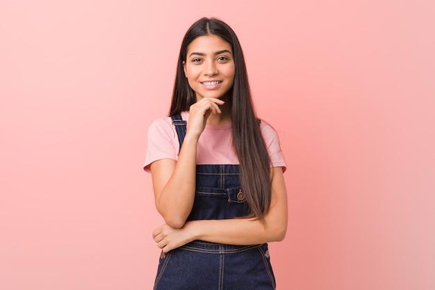Junge hübsche arabische frau, die eine jeans-latzhose trägt, die glücklich und zuversichtlich lächelt und kinn mit hand berührt.