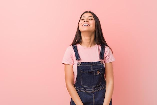 Junge hübsche arabische frau, die eine jeans-latzhose trägt, entspannt und glücklich lachend, hals gestreckt, zähne zeigend.
