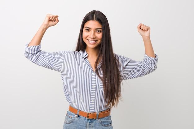 Junge hübsche arabische frau, die kraftgeste mit armen zeigt, symbol der weiblichen macht