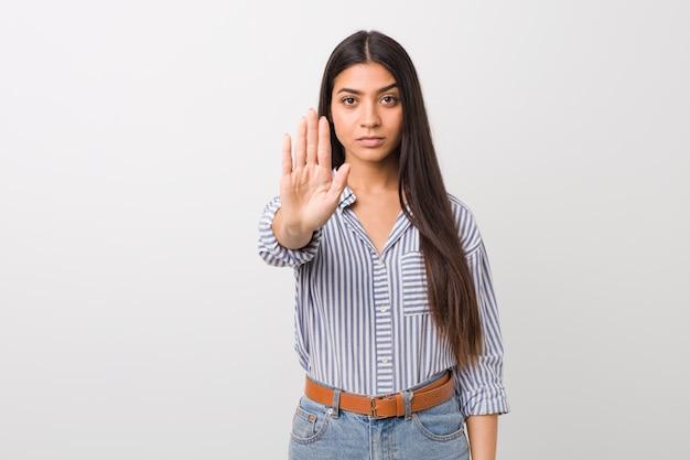 Junge hübsche arabische frau, die mit der ausgestreckten hand zeigt das stoppschild, sie verhindernd steht.