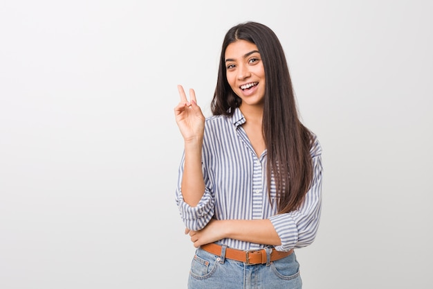 Junge hübsche arabische frau freudig und sorglos, ein friedenssymbol mit den fingern zeigend.