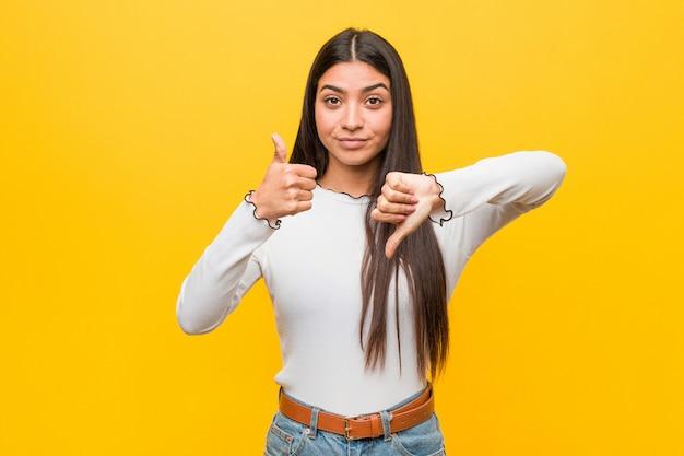 Junge hübsche arabische frau gegen ein gelb, das daumen hoch und daumen unten zeigt, wählen schwierig
