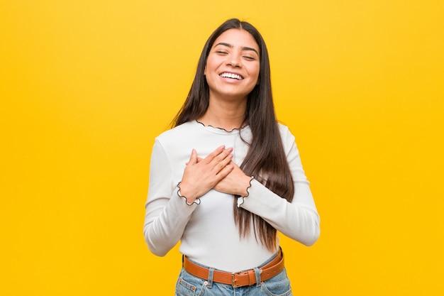 Junge hübsche arabische frau gegen eine gelbe wand lachend, hände auf herzen, konzept des glückes halten.