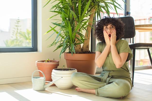 Junge hübsche arabische frau zu hause, mit einer gießkanne und pflanzen
