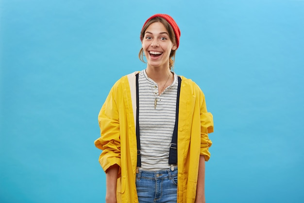 Junge hübsche arbeiterin, die gelbe jacke, jeansoverall und roten hut trägt, der gegen blaue wand aufwirft, die lächeln hat, das glücklich ist, ihre arbeit über haus zu beenden. emotionen, glückskonzept