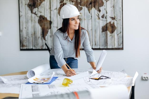 Junge hübsche architektin, die im büro arbeitet