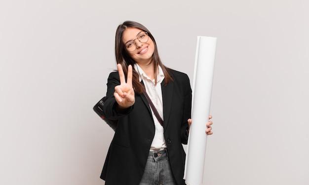 Junge hübsche architektin, die lächelt und freundlich aussieht, die nummer zwei oder die zweite mit der hand nach vorne zeigt und herunterzählt