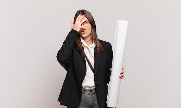 Junge hübsche architektin, die schockiert, verängstigt oder verängstigt aussieht, das gesicht mit der hand bedeckt und zwischen den fingern späht